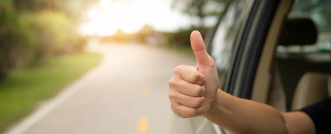 passenger giving a thumbs up as a sign satisfaction from a warrantied vehicle